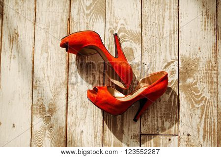 Women's shoes bright red suede on the wooden background.Women's shoes bright red suede on a wooden background.