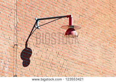 Red lamppost hanging on a red brick wall. Copy space on wall.