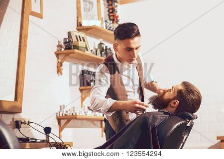 Do everything perfect. Pleasant professional barber holding scissors and cutting beard of his client while doing his job
