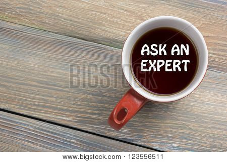 Ask an expert. Coffee cup with message. Office desk table top view
