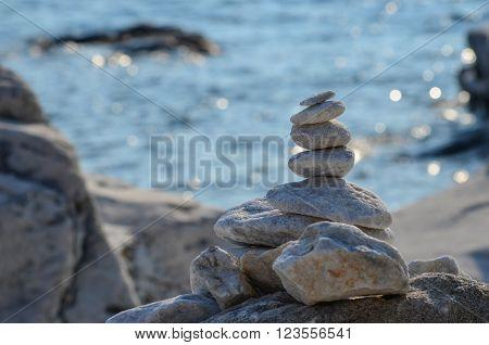Zen stones on rocky beach before sunset against blue bokeh background
