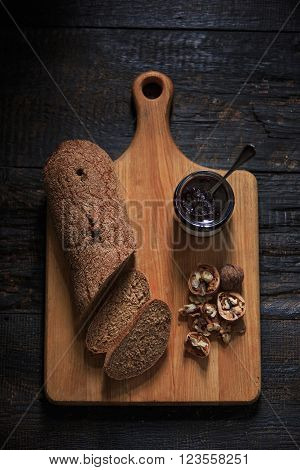The top view of fruity jam and spoon and knife on black wooden table and bread