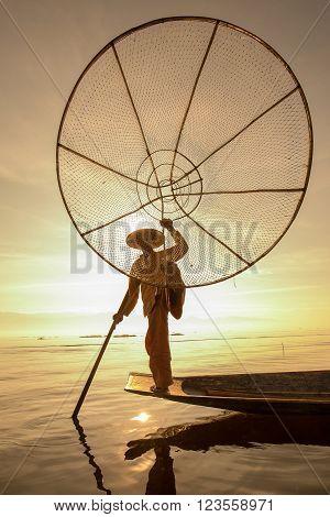 INLE LAKE, MYANMAR - JANUARY 12, 2016: Unidentified Burmese fisherman on bamboo boat catching fish in traditional way with handmade net. Inle lake, Myanmar, Burma