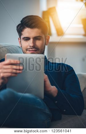 Enjoying his new digital tablet. Close-up of handsome young man using his digital tablet with smile while lying down on the couch at home