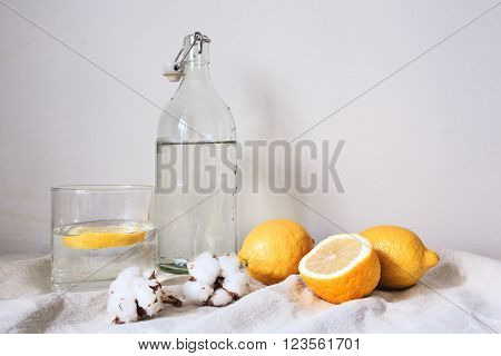 Tasty cool beverage with  fresh lemons on white cotton fabric