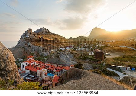 Ancient Genoese fortress in Sudak town. Panorama view at sunset. Crimea, Russia.