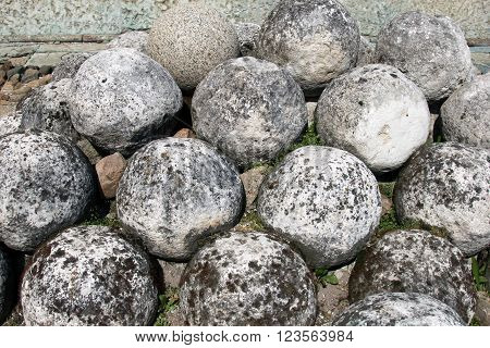 Old cannonballs, a core of ancient tools. Historical sites fortress Velikiy Novgorod, Russia. Stone cannon. Rare weapons of the Slavic wars.