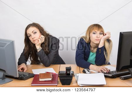 Two Young Employee Of The Office Behind A Desk Looking Sadly Into The Frame