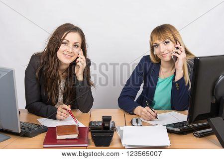 Two Office Workers Talking On The Mobile Phone At His Desk