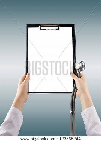 Female doctor's hand holding medical clipboard with blank sheet of paper on blie blurred background. Concept Healthcare And Medicine. Copy space.