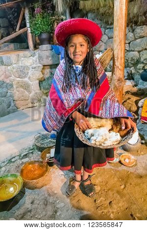 Ollantaytambo, Peru - Circa June 2015: Girl In Traditional Peruvian Clothes Holds A Basket With Alpa