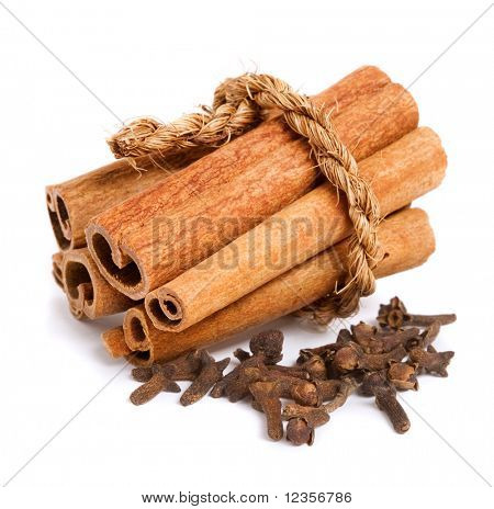 Pile of cinnamon and cloves on white background