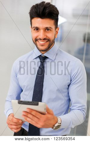 Checking his mail. Young handsome businessman using his touchpad while standing in office.