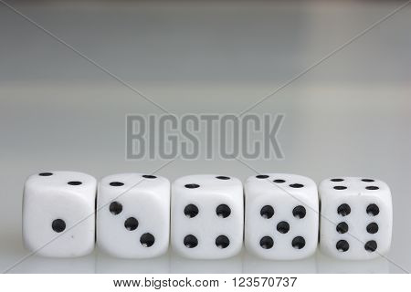 Dice. Playing cubes. Throwing the dice during the game. White cubes arranged in a row. On a white background. There is room for text.