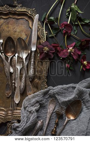 Old vintage ornamented cutlery and antique nickel copper tray on a wooden table