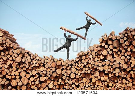 balancing business man on  top of another on  top of large pile of cut wooden logs , lifting heavy log, back view