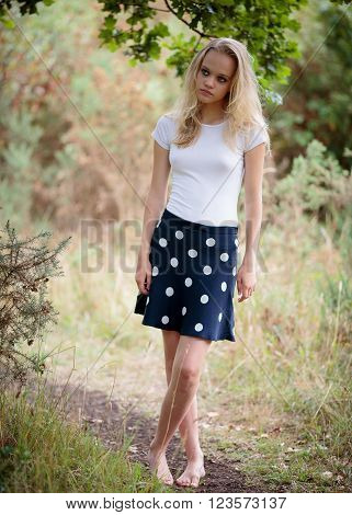 Portrait of a beautiful teenage blond girl with long hair wearing a tight white shirt and a blue skirt outside in a natural wood.