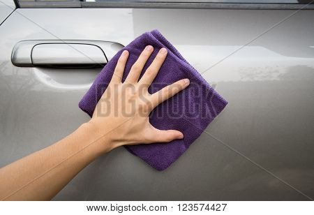 hand holding microfiber cloth polishing gray car