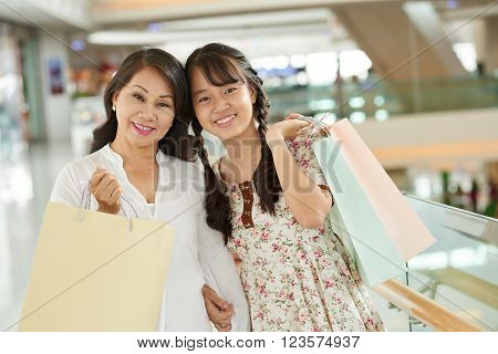 Portrait of happy smiling mother and daughter with shopping bags