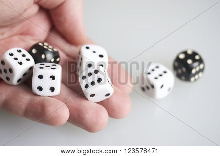Dice in the hand of man. Throwing the dice during the game. Cubes of white and black color on a white background.