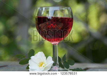 a glass of red wine and a white rose