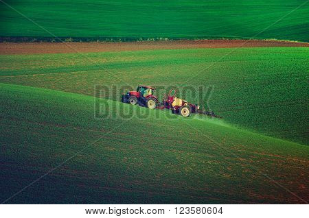 Farm machinery spraying insecticide to the green field, agricultural natural seasonal spring background, vintage retro hipster style