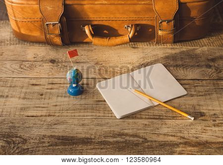 Suitcase, nootbook, pencil, flag on wooden planks. Aim, attainment, target, tourism, travel.