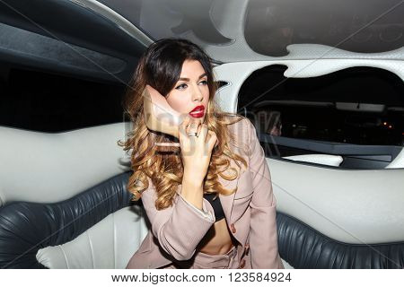 Woman talking on a shoe on the phone in the car with the driver in a pink business suit with bright makeup and shoes with heels sitting in a car, limousine