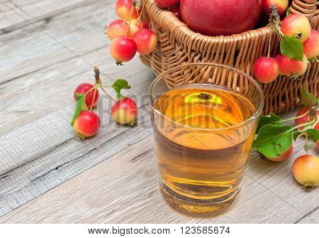 glass of apple juice and a basket of apples. wood background - horizontal photo.