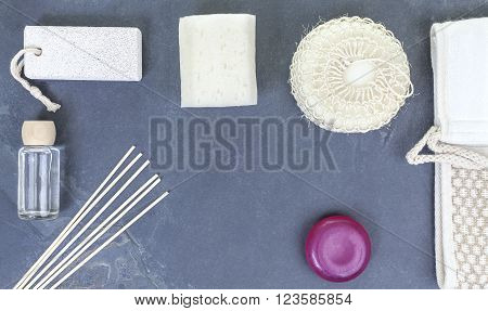Spa flat lay background with sponge, facecloth, aroma sticks, oil; soap, pumice over natural cracked slate.