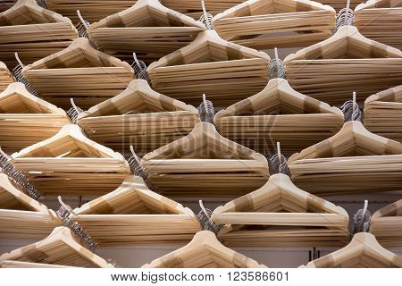 number of empty hangers in the store. Wooden bright hangers for coat and dress
