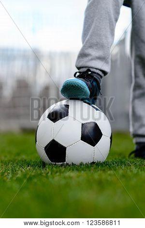 Feet Of Little Boy On Ball On Football Field