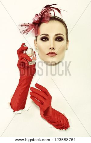 Retro fashion portrait of young woman with red gloves and bottle of perfume, image toned.