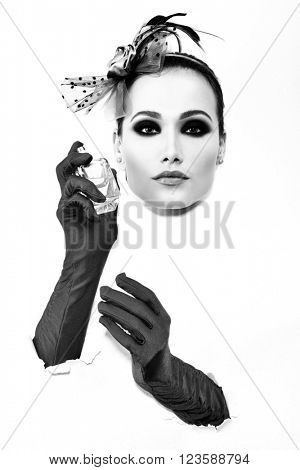 Retro fashion portrait of young woman with gloves and bottle of perfume, black and white.