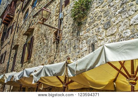 umbrellas and old building in San Gimignano Italy