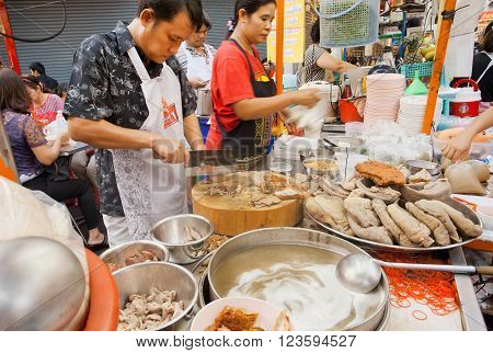 BANGKOK, THAILAND - FEB 14: Workers of street restaurant cooking meat dishes outdoor on February 14, 2016. Population of Bangkok is over 8 million most populous city of Thailand.
