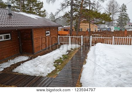 Irkutsk Region< Russia -March,20 2016: Spring sleet in the village. Inner yard of country house Siberia Russia