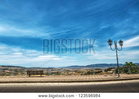 wooden bench and classic lamppost under a blue sky