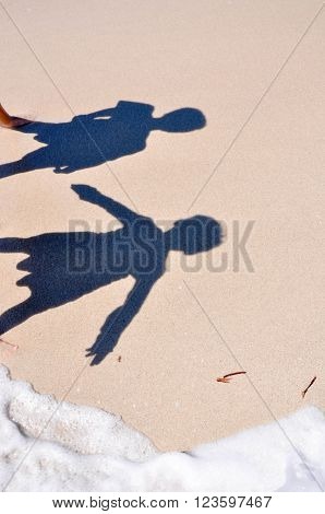 Two shadow silhouettes of children on a sandy beach with foamy ocean wave detail.