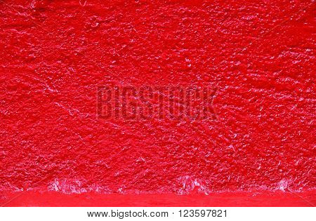 Close up red kerb line or curb stone border on the asphalt road with wet paint. Footpath background.