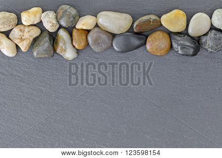 Background texture of beautiful stone, small pebbles on black board slate slabs