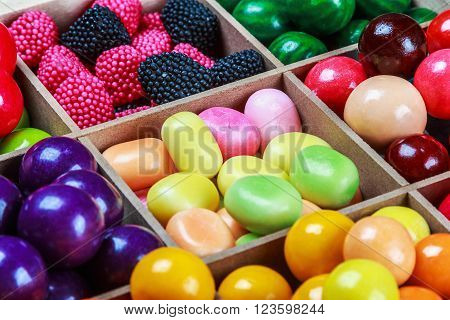 multi colored candy and chewing gum in a wooden box. Focus on the top of the frame