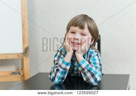 Blond boy sitting at the table at home and learns. The idea of school school home education and developmental activities.