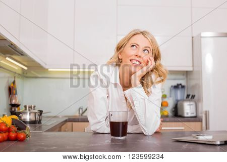 Woman in the kitchen with coffee daydreaming