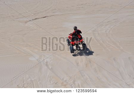LANCELIN,WA,AUSTRALIA-SEPTEMBER 28,2015: Quad bike and rider at the white sand dunes tourist attraction in Lancelin, Western Australia.