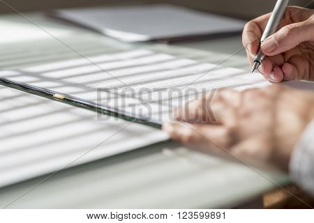 Closeup low angle view of man signing a contract or document with light from the window falling on the paperwork.
