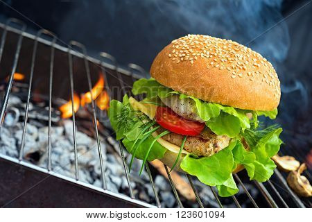 Hamburger - burger with grilled beef, cheese and vegetables on flame bbq
