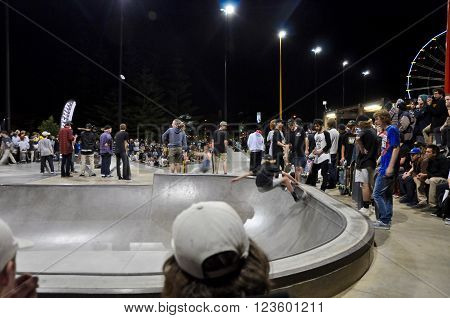 FREMANTLE,WA,AUSTRALIA-SEPTEMBER 30,2015: Skateboarding showcase at night with skater in the bowl and spectators at the Esplanade Youth Plaza in Fremantle, Western Australia.