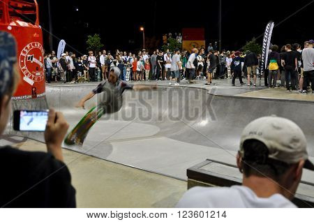 FREMANTLE,WA,AUSTRALIA-SEPTEMBER 30,2015: Skateboarding showcase at night with spectators and skater riding the rails at the Esplanade Youth Plaza in Fremantle, Western Australia.
