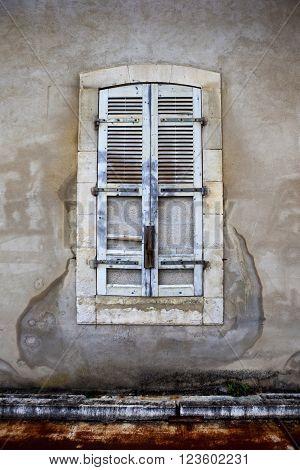 Dead window and broken shutter of a slum